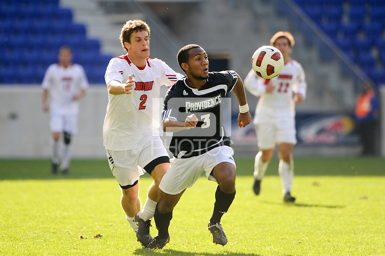 George Hodge (3) of the Providence Friars is cahsed by Charlie Campbell (2) of the Louisville Cardinals. The Louisville Cardinals defeated the Providence Friars 3-2 in penalty kicks after playing to a 1-1 tie during the finals of the Big East Men's Soccer Championship at Red Bull Arena in Harrison, NJ, on November 14, 2010.