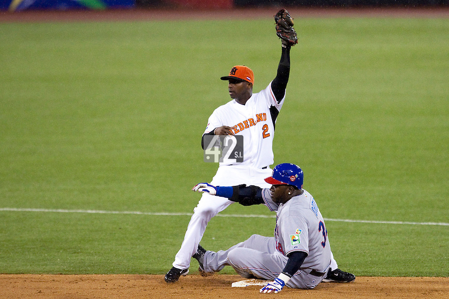 10 March 2009: #34 David Ortiz of the Dominican Republic slides safely into second base with a double as #2 Yurendell DeCaster of the Netherlands catches the ball during the 2009 World Baseball Classic Pool D game 5 at Hiram Bithorn Stadium in San Juan, Puerto Rico. The Netherlands pulled off second upset to advance to the secound round. The Netherlands come from behind in the bottom of the 11th inning and beat the Dominican Republic, 2-1.