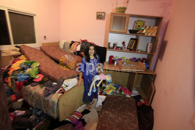 A Palestinian girl inspects her room after the Isreali soldiers raided her family's house in the West Bank village of Aroura near Ramallah, early on June 20, 2014. Israeli authorities have arrested about 300 activists, including 200 members of Hamas, and raided several hundred buildings following the disappearance of three Israeli teenagers last week, according to reports. No organization has claimed responsibility for the disappearance, which Israel blames on Hamas militants. Photo by Issam Rimawi