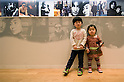 SAITAMA - DEC. 5: Two Japanese children, visiting the John Lennon Museum with their parents, pose in front of a collection of photos of John Lennon and Yoko Ono.  (Photo by Alfie Goodrich/Nippon News)