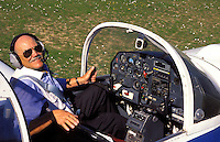 Retired man in the cockpit of his light plane.  France.