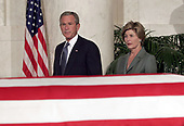 United States President George W. Bush (L) and First Lady Laura Bush approach Chief Justice William Rehnquist's flag-draped casket Sept. 6, 2005 in the Great Hall of the Supreme Court in Washington, DC. Rehnquist's casket will lie in repose at the court until the next morning and he will be buried in a private ceremony at Arlington Cemetery that afternoon. <br /> Credit: Chip Somodevilla / Pool via CNP