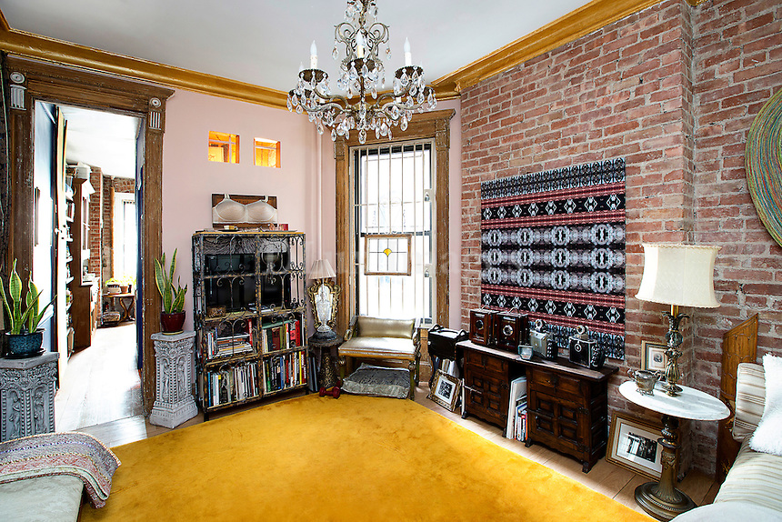 Bright living room with exposed brick wall<br /> <br /> Artist Cynthia Karalla's railroad apartment in a New York City 1910  brownstone filled with antiques and her own artwork.