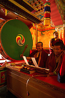 Buddhist monk playing a large drum during the Losar chanting in a monastery in Sikkim India