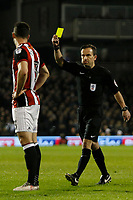 Referee, Keith Stroud shows the yellow card to Enda Stevens of Sheffield United during the Sky Bet Championship match between Fulham and Sheff United at Craven Cottage, London, England on 6 March 2018. Photo by Carlton Myrie.