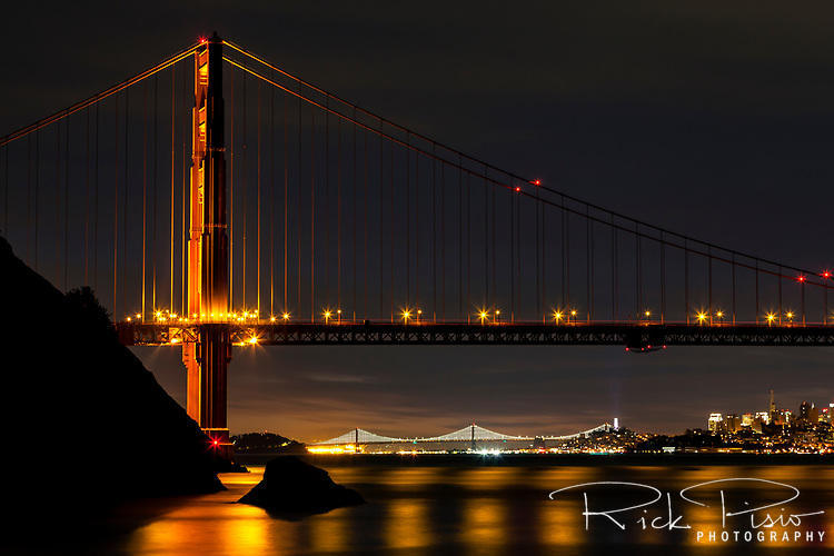 North Tower of the Golden Gate Bridge in the pre dawn hours with the Bay Bridge and San Francisco in the background.
