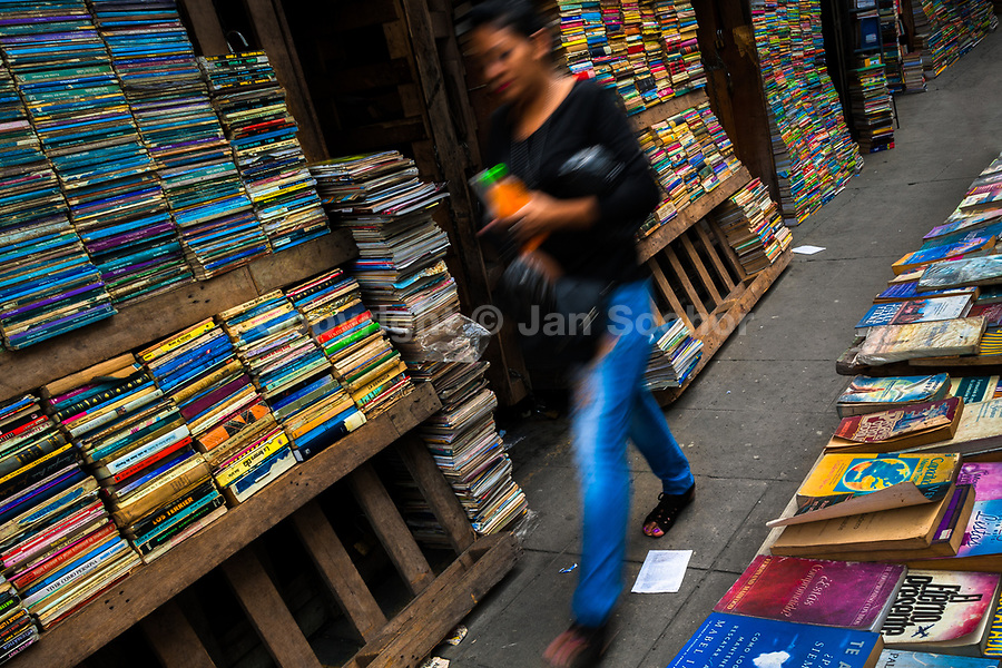 A Salvadoran woman walks along hundreds of used books stacked in shelves on the street in a secondhand bookshop in San Salvador, El Salvador, 12 April 2018. Large collections of worn-out books, mostly textbooks and educational paperbacks, are sold regularly in secondhand bookshops in the center of the city.