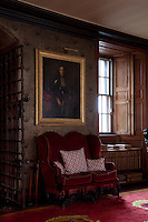A small sofa upholstered in red velvet contrasts with the heavy iron gated doorway to this room. A late 17th century swagger portrait hangs above