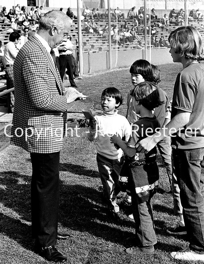 New York Yankee great Joe DiMaggio signing autographs for kids at University of California baseball diamond in Berkeley, Ca (1974 photo/Ron Riesterer)