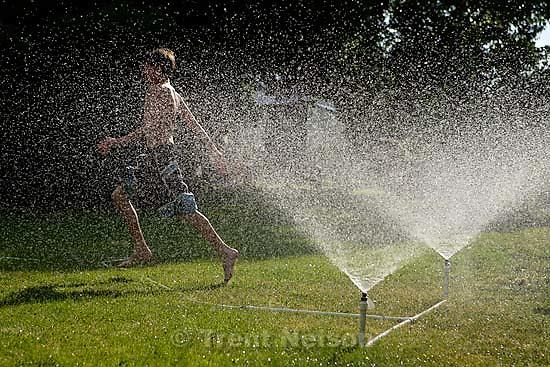 kids running in sprinklers<br />