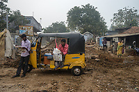 People read newspaper next to a autorickshaw in village Gorikothapally, Telangana, Indiia, on Friday, February 8, 2019. Photographer: Suzanne Lee for Safe Water Network