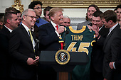 United States President Donald J. Trump receives a football jersey with his name on it from quarterback Easton Stick, right, as he welcomes the 2018 Division I FCS National Champions: The North Dakota State Bison in the State Dining Room of the White House on March 4, 2019 in Washington, DC.<br /> Credit: Oliver Contreras / Pool via CNP
