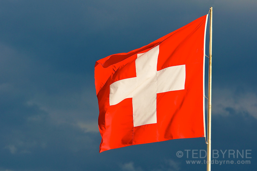 Bright Swiss flag against a dark sky