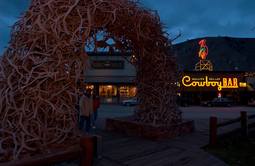 Passers-by peer through one of four elk antler archesh on the town square in Jackson, Wyo., as the lights of the Million Dollar Cowboy Bar shine behind. (Kevin Moloney for the New York Times)