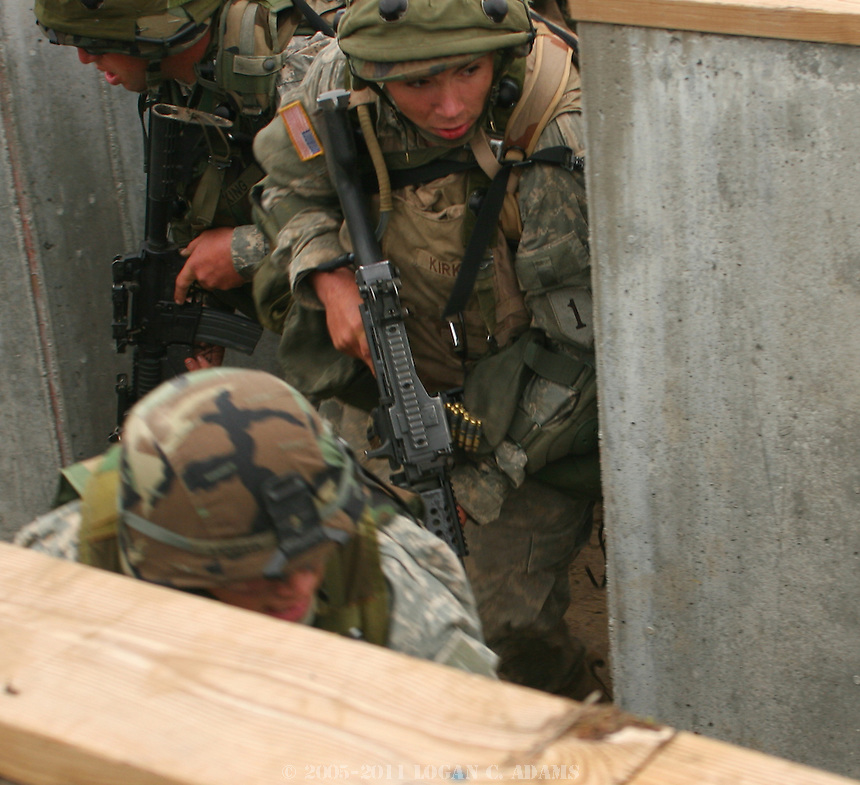 """Soldiers of the 1st Battalion, 28th Infantry Regiment of the 1st Infantry Division practice a trench-clearing maneuver in training at Fort Riley, Kan., on Sept. 11, 2006. The soldiers had been out the two previous days performing training missions with blank rounds, during one of which they """"captured"""" a high-ranking Al-Qaida leader. ..The soldiers attacked with two squads, one providing cover fire while the other advanced, went over a ring of concertina wire and cleared the trenches room by room.  They suffered two """"casualties"""" in the assault, neither were severe. Other soldiers hid in the trench, acting as enemy, and provided resistance...Four students and a professor from the A.Q. Miller School of Journalism and Mass Communications observed the exercise and interviewed many of the soldiers once it was completed."""