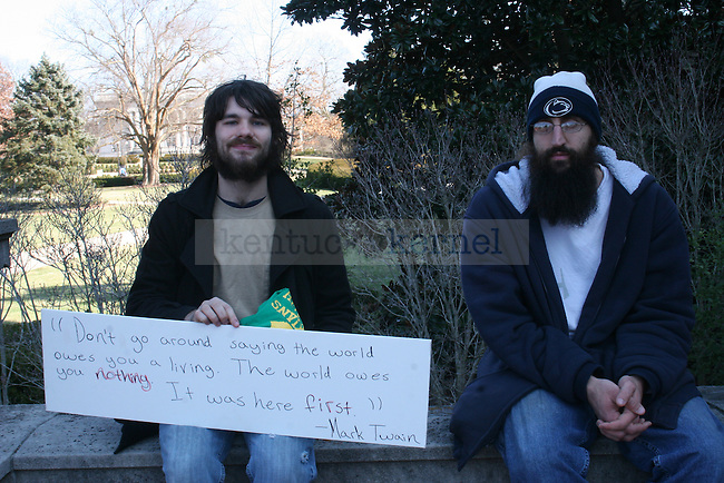 Berea College students Shawn Hutchins (left) and Bradley Niederriter sit with their protest sign, quoting author Mark Twain, during the I Love Mountains Day rally at the Capitol Building in Frankfort, Ky. on Thursday, Feb. 14, 2013. Photo by Adam Pennavaria | Staff