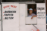 Oscar DeLeon looks out of his food stand on the street in Matamoros Mexico. Some seasonal workers in the Tampa area call Matamoros home.