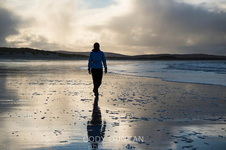 Woman walks on Traigh Hornais beach, North Uist, Outer Hebrides, Scotland