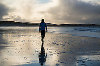 Woman walks on Traigh Hornais beach, North Uist, Outer Hebrides, Scotland