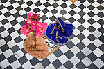 Rajasthani women in colorful dresses sitting on marble tiled floor in temple in Blue City, Jodphur, Rajasthan, India --- Model Released