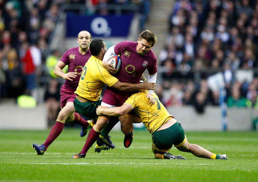 Photo: Richard Lane/Richard Lane Photography. England v Australia. QBE Autumn Internationals. 17/11/2012. England's Toby Flood is tackled by Australia's Kurtley Beale and Michael Hooper.