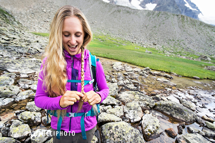 A female backpacker stands smiling while braiding her hair