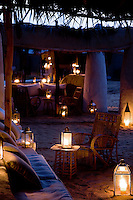 Lit only by lanterns, the covered terrace of the lodge presents an entrancing scene on a warm and balmy evening