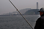 April 5, 2011, Okumamachi, Japan - A lone angler casts the line at the sea with Fukushima No.1 nuclear power plant in the background along the Pacific coast some 120 miles northeast of Tokyo in this July 29, 2009, file photo. The decision by Tokyo Electric Power Co. to dump radioactive water from its crippled plant into the sea angered fishermen. The company known as TEPCO began discharging 11,500 tons of water on Monday to make room to store more highly contaminated fluids in the crippled plant. Fishermen in the area asked the utility giant to stop releasing contaminated water after radioactive iodine and cesium were found in fish caught in the waters nearby. (Photo by Natsuki Sakai/AFLO) [3615] -mis-