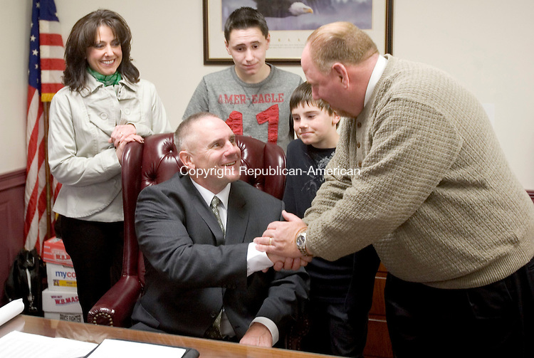 WOLCOTT, CT. 17 March 2012-031712SV01-Mayor Tom Dunn turns over his desk to Bob Stoeckert, Irish Mayor for the Day, at town hall in Wolcott Saturday. Stoeckert's family stands behind him from left, Kelly Stoeckert, his wife, Bobby, 12, and Matt, 9 , his sons..Steven Valenti Republican-American