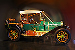 Museum quality green and yellow Pope Hartford Roadster with carmel colored leather seats and trim and a tan fabric top photographed from the side against a blurred background camouflaging the environment at J.K.Lilly III Antique Automoble Museum, Heritage Museum and Gardens, Sandwich, MA. Tool box sits on passenger step and four spare tires are fastened at the rear of the vehicle.