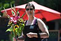 NWA Democrat-Gazette/J.T. WAMPLER Alison Trumpore of Fayetteville carries a bouquet of fresh flowers she purchased Saturday June 10, 2017 at the Fayetteville Farmer's Market. The market is held every Tuesday, Thursday and Saturday on the Fayetteville square.