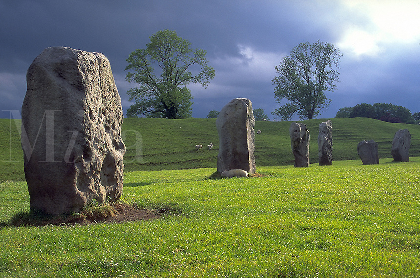 Enormous stone pillar altar specifically aligned for spiritual worship to ancient Godsand Goddesses; clouds; green grass; trees; ancient religions, meadow, landmarks, anthroplology, civilizations, standing stones. Aveberry, England.