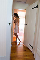 Woman wearing negligee standing in hallway<br />
