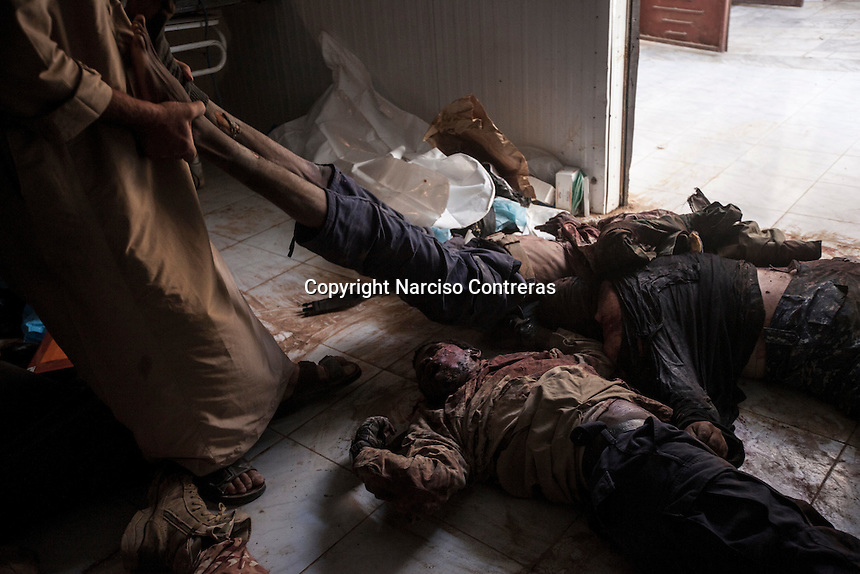 Sunday 22, May 2016: The body of a dead ISIL fighter is dragged among its dead comrades at the morgue of Misrata, Libya.