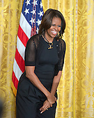 First Lady Michelle Obama enjoys a laugh as she and United States President Barack Obama welcome members of the United States teams and delegations from the 2014 Olympic and Paralympic Winter Games in Sochi to the White House in Washongton, D.C. on Thursday, April 3, 2014.<br /> Credit: Ron Sachs / Pool via CNP