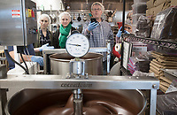 NWA Democrat-Gazette/CHARLIE KAIJO Michelle Pribernow of Fayetteville, Danielle Lyman of Bentonville and Rocky Johnson of Branson, Mo. (from left) watch as a melanger grinds cocoa nibs and sugar to make chocolate during a chocolate making class, Saturday, March 16, 2019 at Markham & Fitz Chocolate in Bentonville. <br /> <br /> Attendees participated in a two-hour hands-on chocolate making class showing the 8-day process of making chocolate from scratch. They learned how to sort, winnow, start batches to grind, temper and mold chocolate bars.