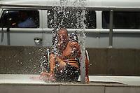 RIO DE JANEIRO, 05.12.2013 - Cadeirante se refresca em fonte na Av. Praça Isabel no Rio de Janeiro na tarde desta quinta-feira. Esta quinta-feira está sendo um dos dias mais quentes de 2013 no Rio de Janeiro. De acordo com o  Instituto Nacional de Meteorologia a temperatura máxima chegou a 39,8°C na estação de Santa Cruz. na zona oeste carioca. De acordo com as medições deste órgão,  a maior temperatura deste ano na cidade do Rio foi de 40,9°C, em 8 de janeiro, na região da praça Mauá, no centro da cidade. No dia 12 de novembro, a temperatura chegou aos 40,1°C neste local.  . (Foto: Amauri Nehn / Brazil Photo Press).