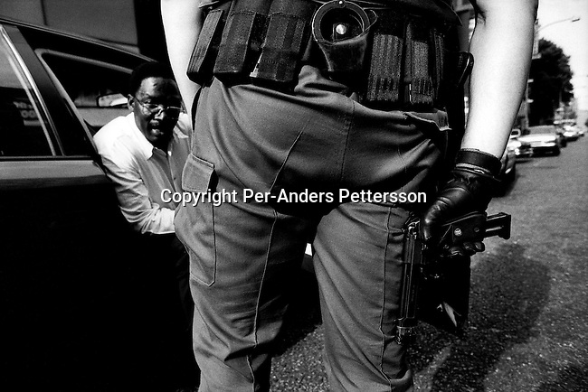 Daniel Lieberman, a Flying Squad police officer, draws his gun after stopping a black motorist on February 13, 1999 in Hillbrow, Johannesburg, South Africa. Flying Squad is a rapid response unit working in South Africa's larger cities, and they have a reputation for being hard on suspected criminals. South Africa has some of the highest crime statistics in the world, especially in car highjacking, armed robberies and rape. (Photo by: Per-Anders Pettersson)