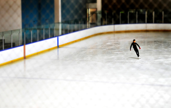Young girl skating alone on an ice rink.