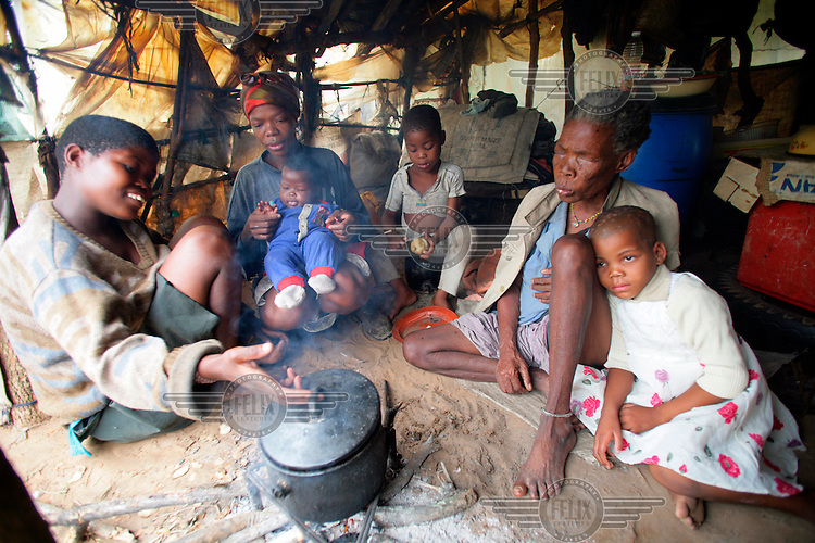 A family cooking a meal in a poor community.