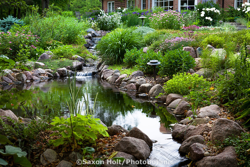 Back yard garden pond with stream edged with rocks and perennials - Barrington Hills, Illinois garden