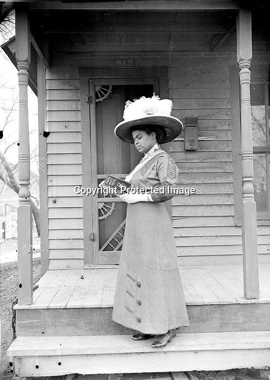 MAMIE GRIFFIN AT 915 U STREET, 1914. The house number 915 is clearly visible above the plumed hat of this well-dressed matron. The close-up view displays the lace detailing of her dress and the title of her book, The Wife of Monte Cristo. The book was a sequel (by a different author) to the immensely popular The Count of Monte Cristo by Alexandre Dumas.<br />