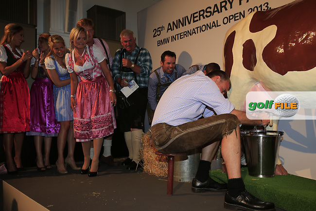 Marko Kausler takes his turn at the milking competition between the boys and girls at the BMW 25th Anniversary Party held in Rilano 6 Palais Lehnbach in Munich on Friday night of the 2013 BMW International Open held on the Eichenried Golf Club, Munich, Germany. 21st June 2013<br /> (Picture: Eoin Clarke www.golffile.ie)