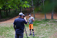 """Brock Wagner (from left) films Rich Drew as he caps an episode of his Youtube show by dancing to a Shakira song he found inspiring, Thursday, May 21, 2020 at Slaughter Pen bike trail in Bentonville. <br /> <br /> Rich Drew, founder of the Rider Series MTB Skills Clinic, filmed an episode of his Youtube channel, Richdrew, where he provides how-to tutorials on riding to his viewers. <br /> <br /> He started the channel in January before the pandemic sent the country into lockdown, shuttering his ride series for two months. <br /> <br /> The shutdown gave him the opportunity to pivot harder towards his channel, which started at about 1,900 viewers, ballooning to 22.6 thousand. <br /> <br /> """"It was tough for me because that was my family's main revenue source. Thankfully, they're coming back,"""" he said of his class regulars. Saturday will be his second class since jumpstarting his in-person series again.<br /> <br /> He will hold his second class, MTB 101 Fundamentals, on Saturday from 8am to noon and 1pm to 5pm at a field in Memorial Park behind the basketball courts. He said they will adhere to CDC guidelines of social distancing. Check out nwaonline.com/200522Daily/ for today's photo gallery. <br /> (NWA Democrat-Gazette/Charlie Kaijo)"""