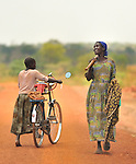A cyclist and a woman with a hoe on a newly build road in northern Uganda.  The road was constructed with community labor under a U.S. AID and Winrock International's $30 million NUDEIL's construction grant.  The impoverished region is now peaceful and beginning a recovery from a long civil war, and brutal insurgency by the Lord's Resistance Army.