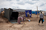 A female Syrian refugee sweeps dust from the ground her tent as refuse collectors pick up rubbish from bins in the Domiz refugee camp in Iraqi-Kurdistan. The camp, run by the UNHCR and International Rescue Committee, is home to around 4,500 refugees who have fled from the ongoing Syrian civil war with up to 400 new inhabitants arriving every day.  Built on the site of a former Iraqi Army base that was bombed during the 2003 Coalition forces invasion of Iraq, the camp was cleared of cluster bombs and unexploded ordnance by the Mines Advisory Group (MAG), a demining NGO working in Iraqi-Kurdistan.