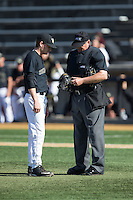 Wake Forest Demon Deacons starting pitcher Drew Loepprich (23) looks on as home plate umpire John Haggerty inspects his glove during the game against the Florida State Seminoles at David F. Couch Ballpark on April 16, 2016 in Winston-Salem, North Carolina.  The Seminoles defeated the Demon Deacons 13-8.  (Brian Westerholt/Four Seam Images)