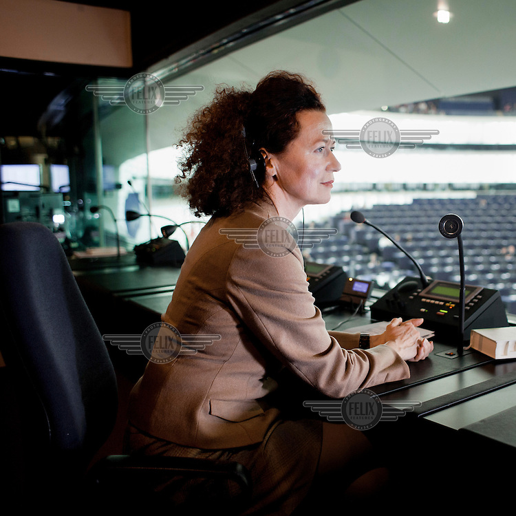 Translator Susan Altenberg seated in a translator's booth at the European Parliament in Strasbourg. Every month she, along with thousands of other parliamentary staff, travels between the three sites of government in Brussels, Strasbourg and Luxembourg.