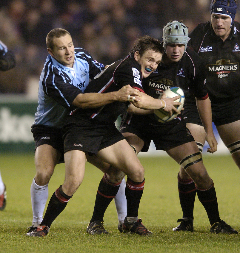 Photo. Jed Wee..Edinburgh Rugby v Newcastle Falcons , Heineken Cup, 11/12/2004..Edinburgh's Rory Lawson is tackled by Newcastle's Hall Charlton.