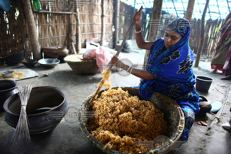 30 year old Rekha Rani making a sweet with puffed rice   in her small factory at her home in Ilisha, Barisal. She has received a microfinance loan and business training from IFAD (International Fund for Agricultural Development).